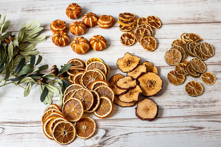Faux greenerybranches, dried mandarins, orange slices, and apple, lemon and lime slices on a table.