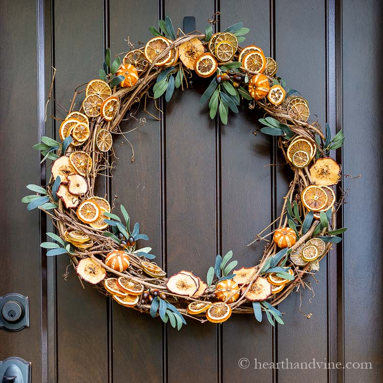 A grapevine wreath base with faux greenery and dried fruit slices glued all around.