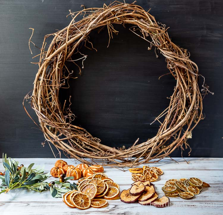 Empty grapevine wreath, faux greenery, dried mandarins, orange slices, and apple, lemon and lime slices on a table.