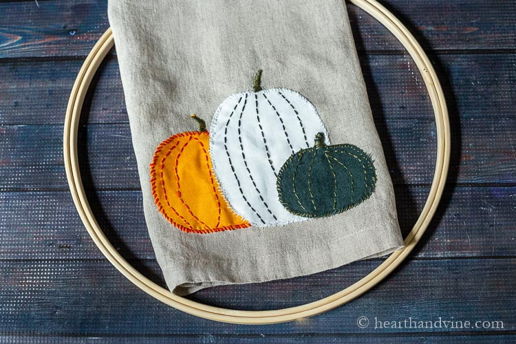 Appliqued pumpkin towel with embroidery hoop underneath.