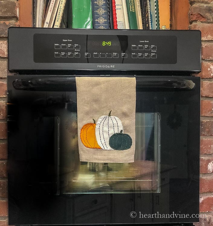 Pumpkin tea towel hanging on the oven door.