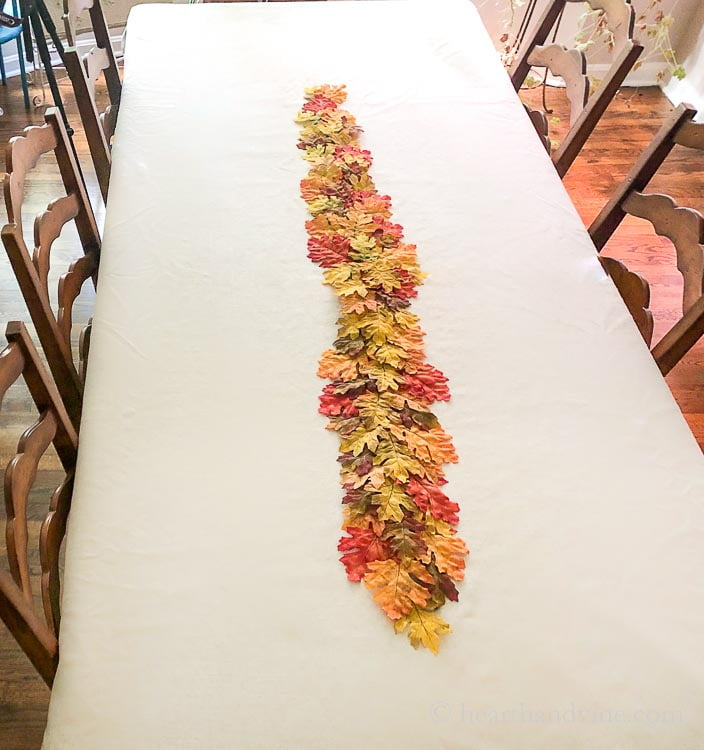 A faux leaf fall table runner a dining room table from above.
