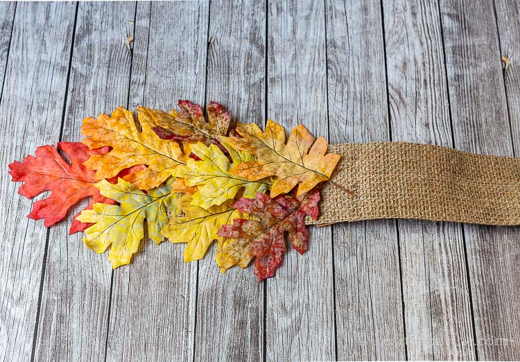 One end of the fall table runner with leaves glued to the end of a burlap ribbon.