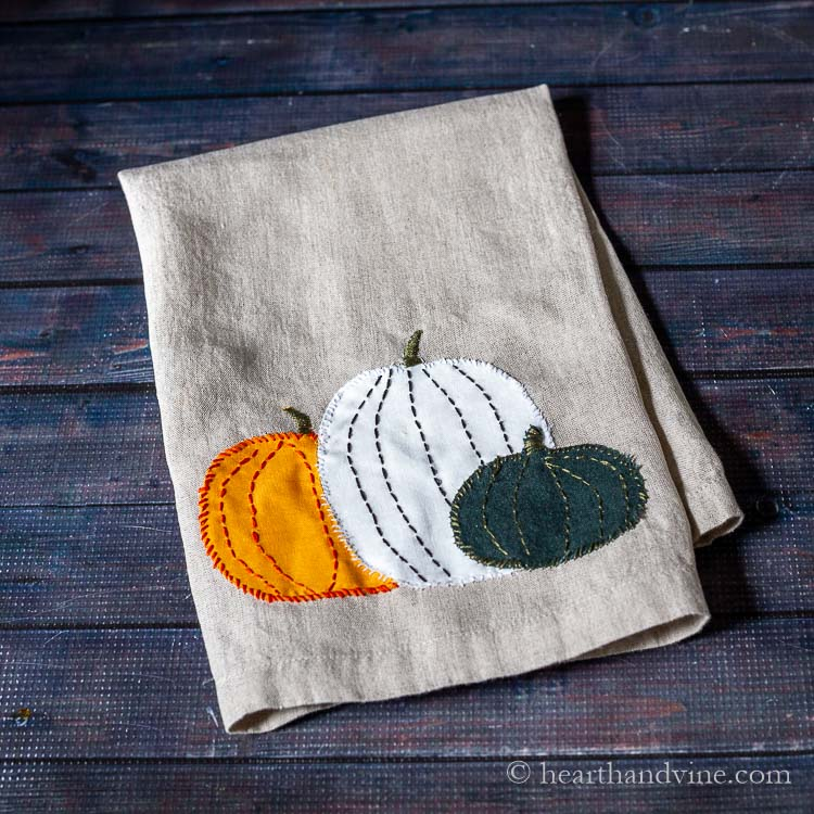 Three pumpkins appliqued onto a linen tea towel. One is orange, one white and the third is dark green. Each is hand embroidered with thread in coordinating and contrasting colors.