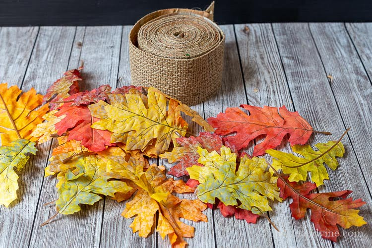 Burlap ribbon next to some faux fall leaves.