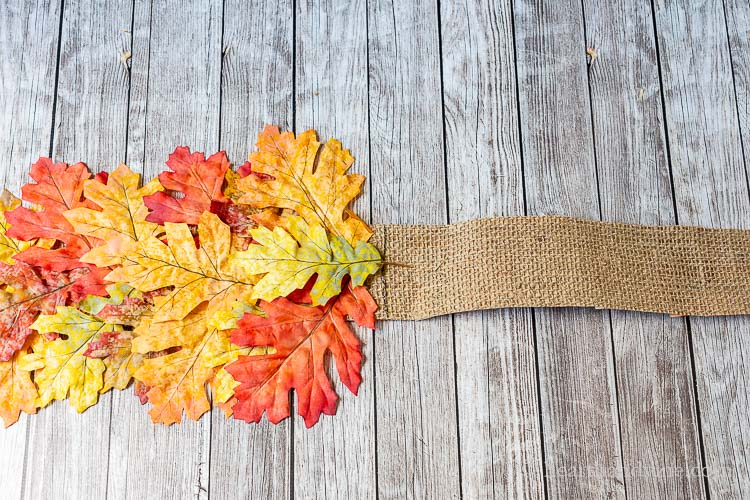 Autumn colored artificial leaves glue to a burlap ribbon up to a black line.