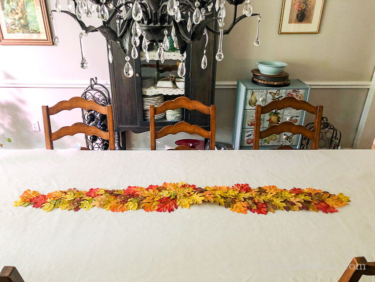 A faux leave fall table runner on a cream tablecloth table in the center.