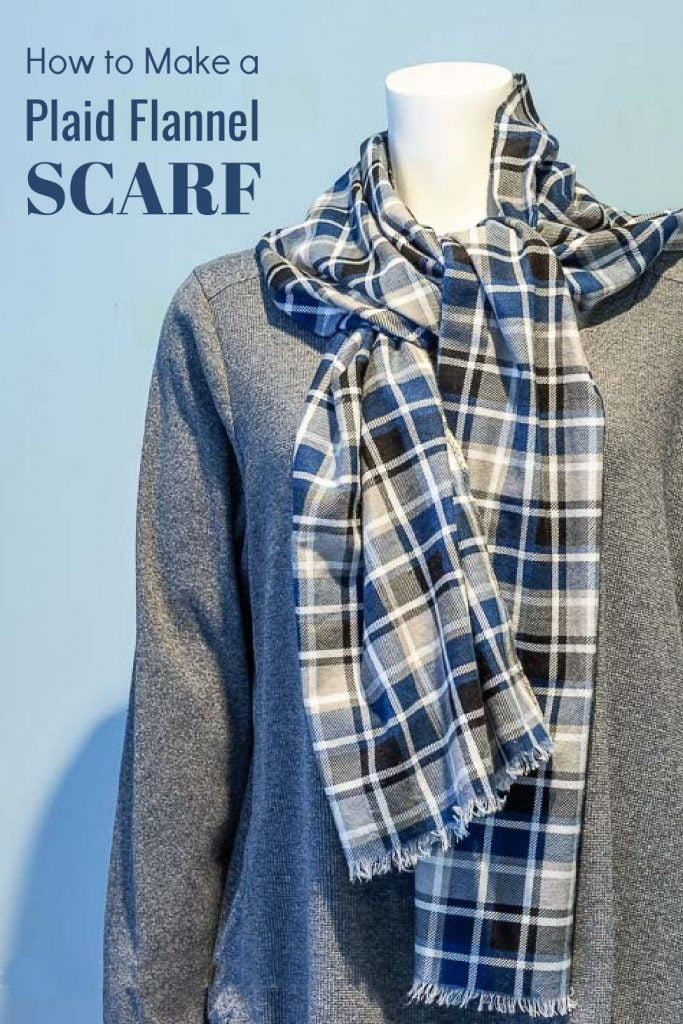A blue, black, white and gray plaid flannel scarf tied around a mannequins neck.