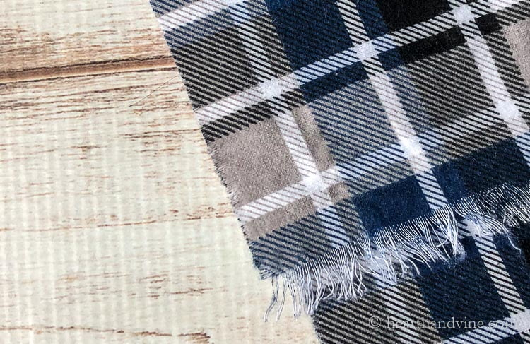 Frayed edge of side of DIY flannel scarf.