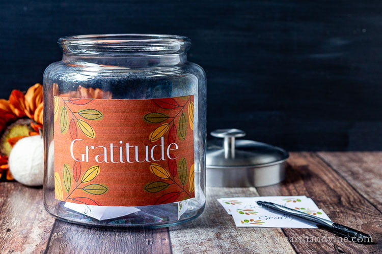 Gratitude jar with the lid off sitting next to some grateful cards and a pen.