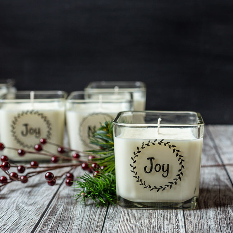 A candle with the word Joy in a wreath on front surrounded by faux greenery and red berries.