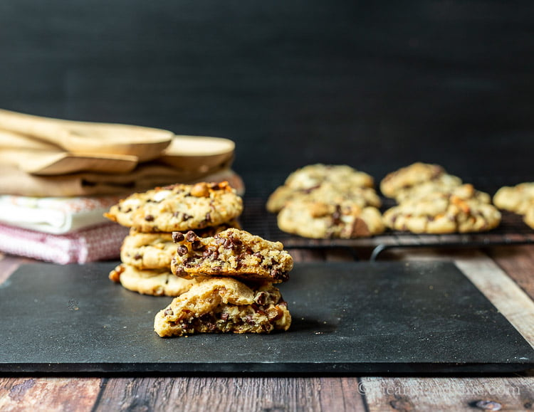 Kitchen sink cookie split in half in front of a stack of tea towels, wooden spoons and a rack of cooling cookies.