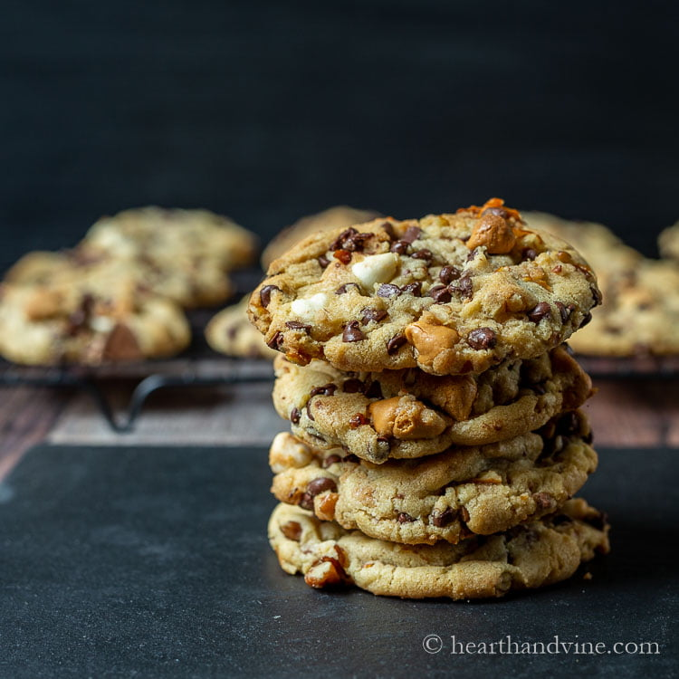 Stack of kitchen sink cookies in front of a cooling rack of same cookies.