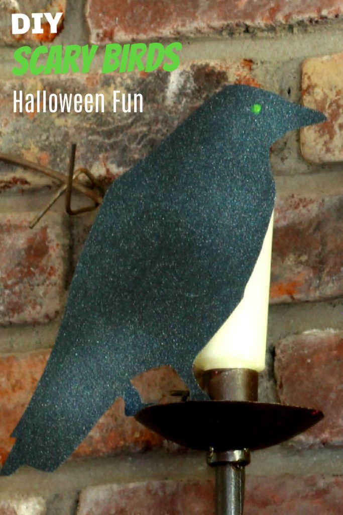 Black paper bird on candlestick.