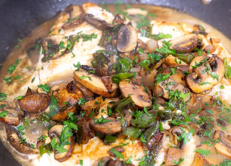 Large pan with chicken, mushrooms, shishito peppers and chopped fresh parsley on top.