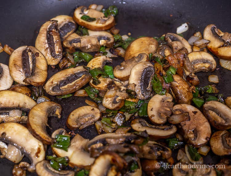 Mushrooms, onions and chopped shishito peppers sautéing in a large pan.