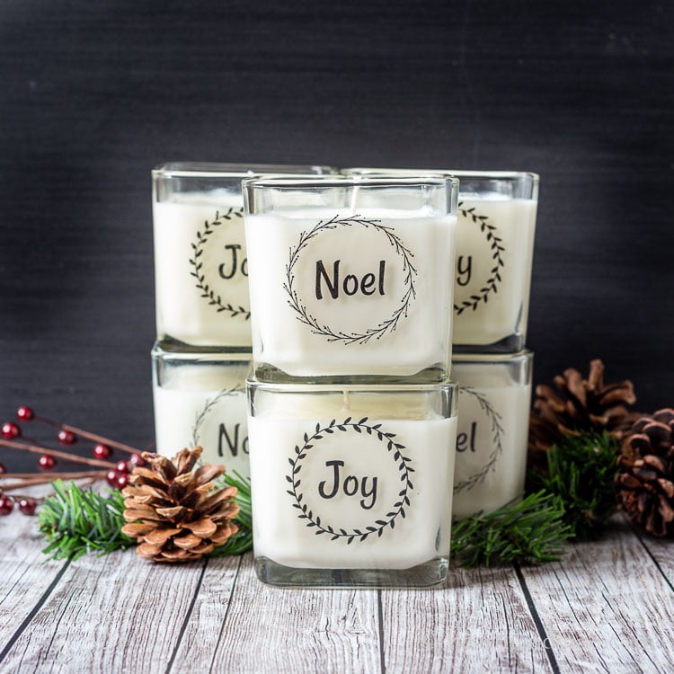 Stacked Christmas candles with packing tape labels containing the words Noel and Joy.
