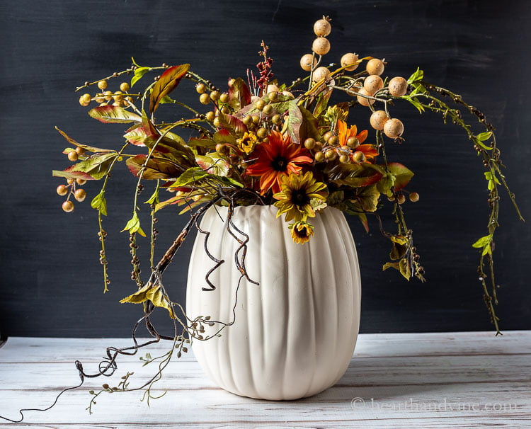 White pumpkin vase with several fall colored artificial flowers, berries and vines.