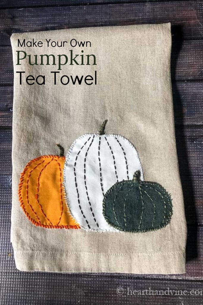 Linen towel with pumpkins appliqued at the bottom.