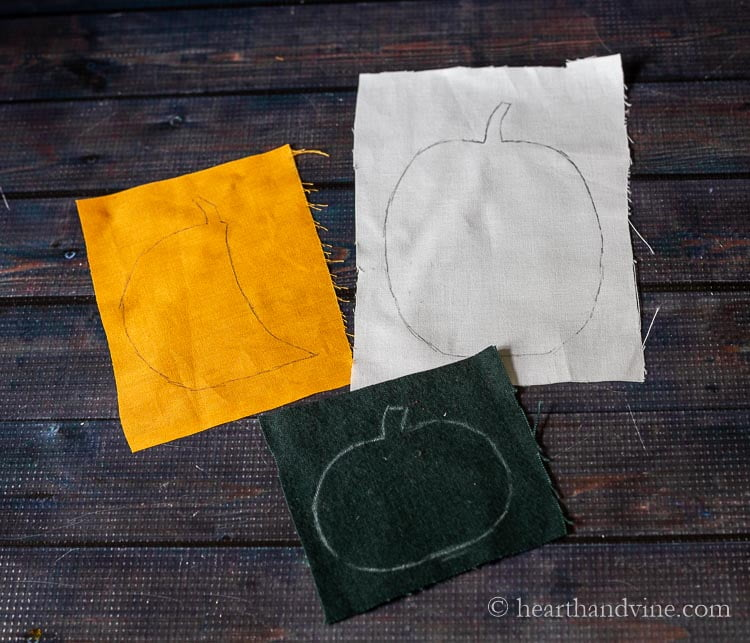 Orange, white and green fabric swatches with whole and partial traced pumpkin graphics.