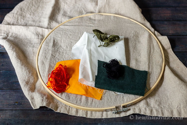 A linen tea towel in an embroidery hoop with pieces of fabric in orange, white and dark green on top and coordinating embroidery threads.