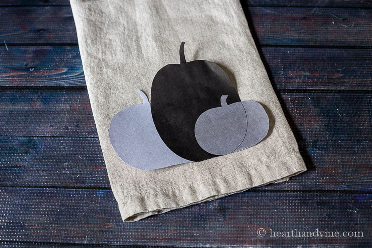 A trio of paper pumpkins set on a fold tea towel.