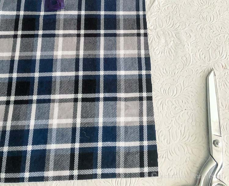 Flannel plaid fabric edge and a pair of sewing scissors.