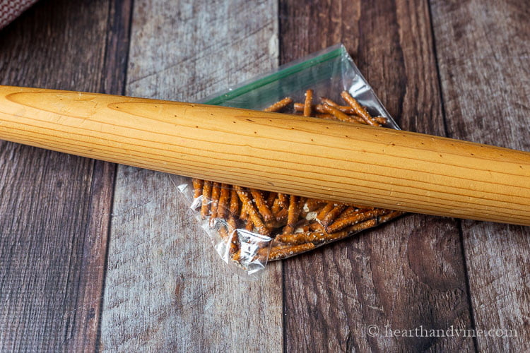 Wooden rolling pin crushing a bag of pretzels.