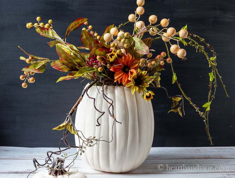 Tall white pumpkin acting as a vase with several artificial flowers and vines coming out the top.