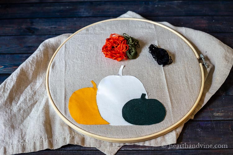 An orange, white and green pumpkin fabric cut out glued to a linen towel and placed in an embroidery hoop with colored thread piles on top.