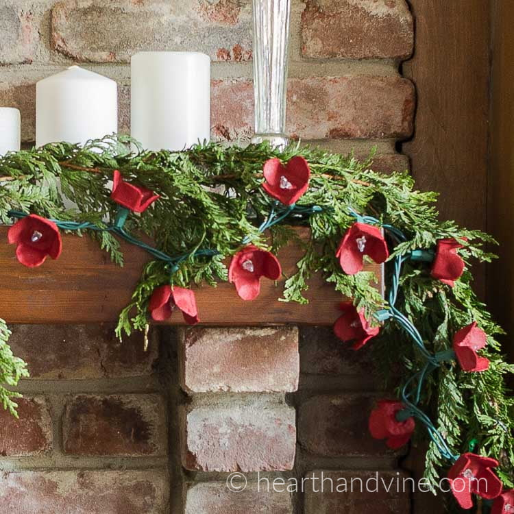 Egg carton flower garland with cedar on the mantel.