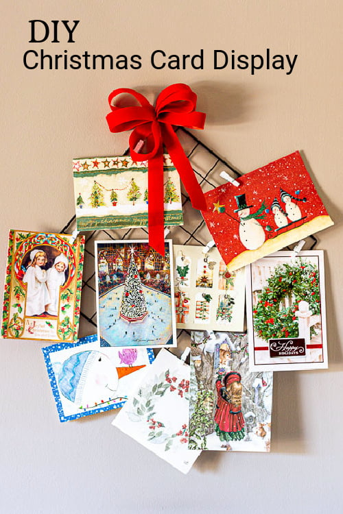 Christmas card holder with red bow and mini clothespins fill with Christmas cards.