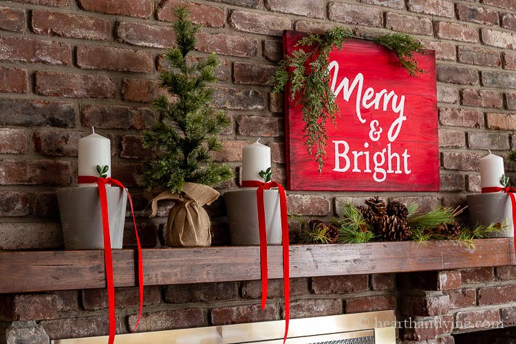 Side view of fireplace mantel decorations with a red and white sign that says Merry & Bright above pine and pine cones. Gray painted clay pots with white pillar candles wrapped with red velvet ribbon and a sprig of box wood in the ribbon. Two small faux evergreen trees are on the side with burlap bases.