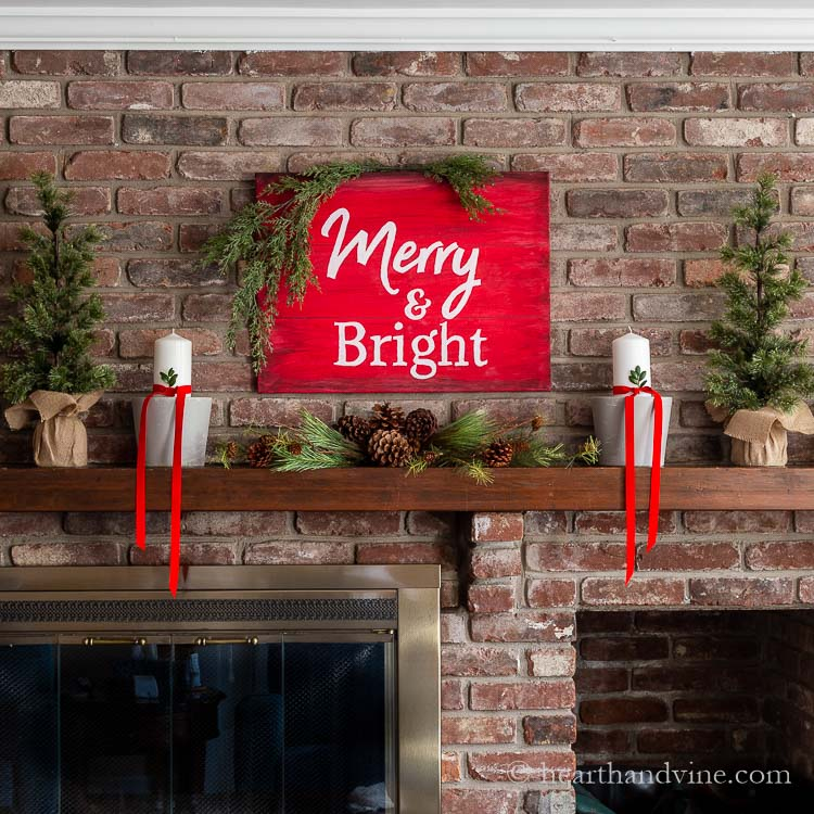 Fireplace mantel decorations with a red and white sign that says Merry & Bright above pine and pine cones. Gray painted clay pots with white pillar candles wrapped with red velvet ribbon and a sprig of box wood in the ribbon. Two small faux evergreen trees are on the side with burlap bases.
