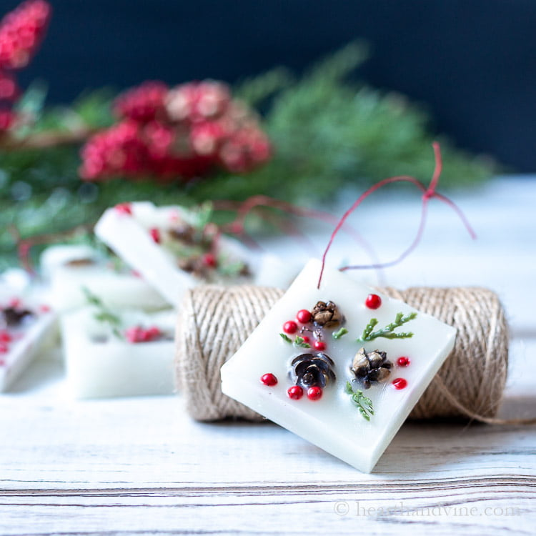 Square wax ornament with min pinecones, red berries and fake greenery leaning on a roll of twine.