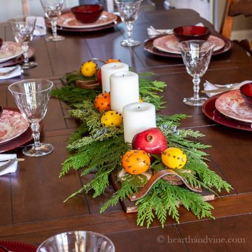 Pallet centerpiece with white candles, cedar branches, orange & lemons studded with cloves and pomegranates