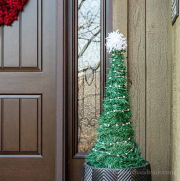 Faux Christmas tree in an outdoor planter with a white pom pom on top.