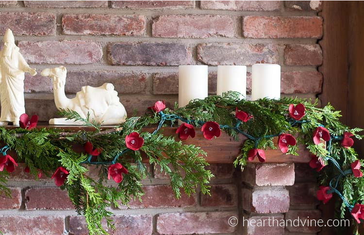 Egg carton flower garland on wooden mantel corner.