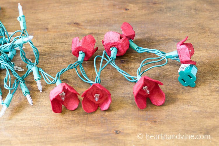 Red egg carton flowers on string of Christmas lights.