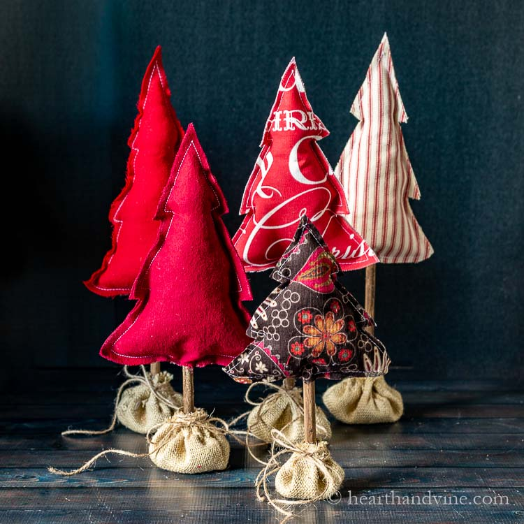 Five fabric Christmas trees in burlap sacks on a table.