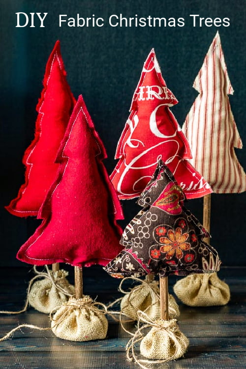 Five different size fabric Christmas trees in burlap sacks on a table.