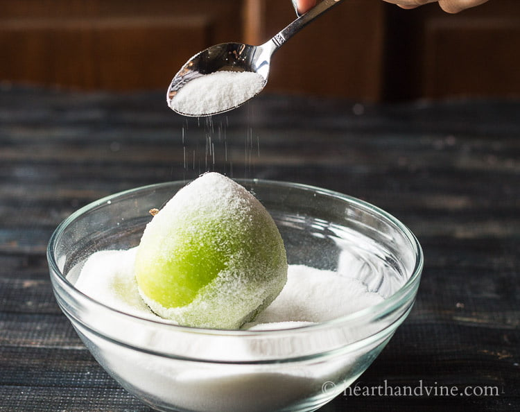 Green apple in a bowl of sugar and a spoon overtop dusting the sugar on.