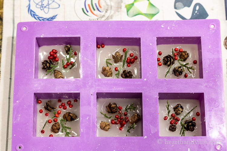 Six cell square soap mold with a small amount of beeswax topped with faux red berries, evergreens and mini pine cones.