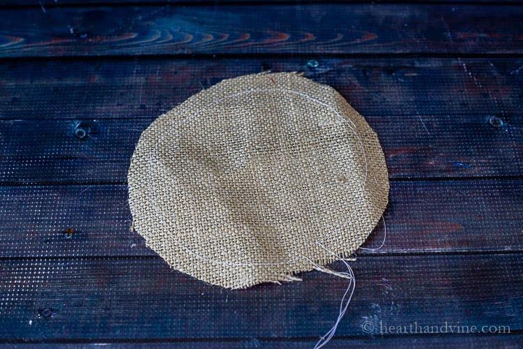 Round of burlap with basting stitches.