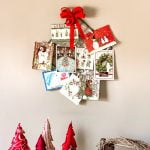 Christmas card holder on wall with cards above a dresser with stuffed fabric trees and a basket.