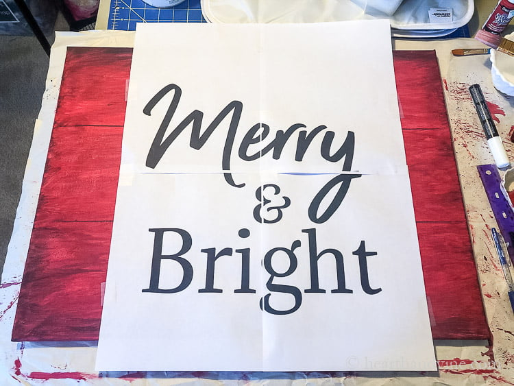 A large computer print out on four pages with the words Merry & Bright on top of a red painted canvas.