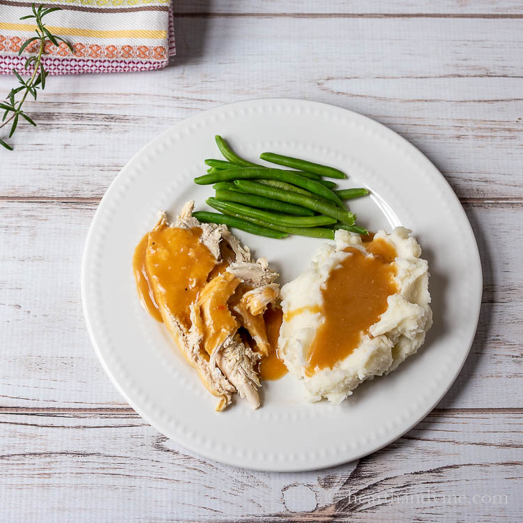 Plate with chicken and mashed potatoes with gravy and green beans on the side