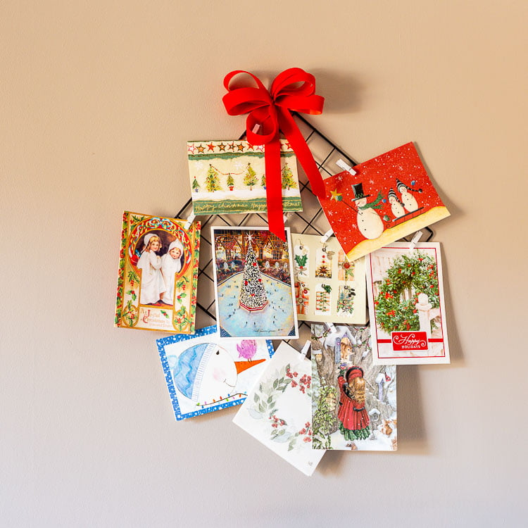 Hanging Christmas card holder with a red bow and several cards on the wall.