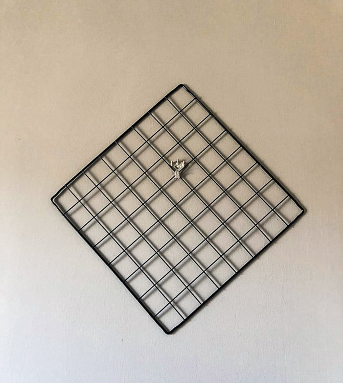 Wire grid square hanging on the wall.