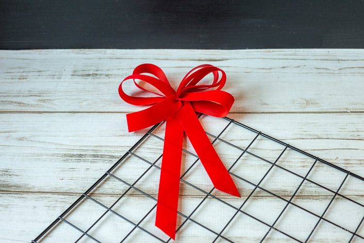 Wire grid square with a red velvet bow tied on to the top corner.